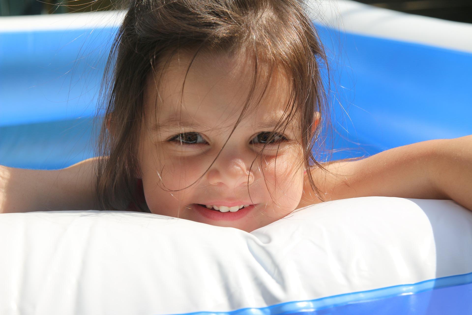Kind im Planschbecken lächelnd