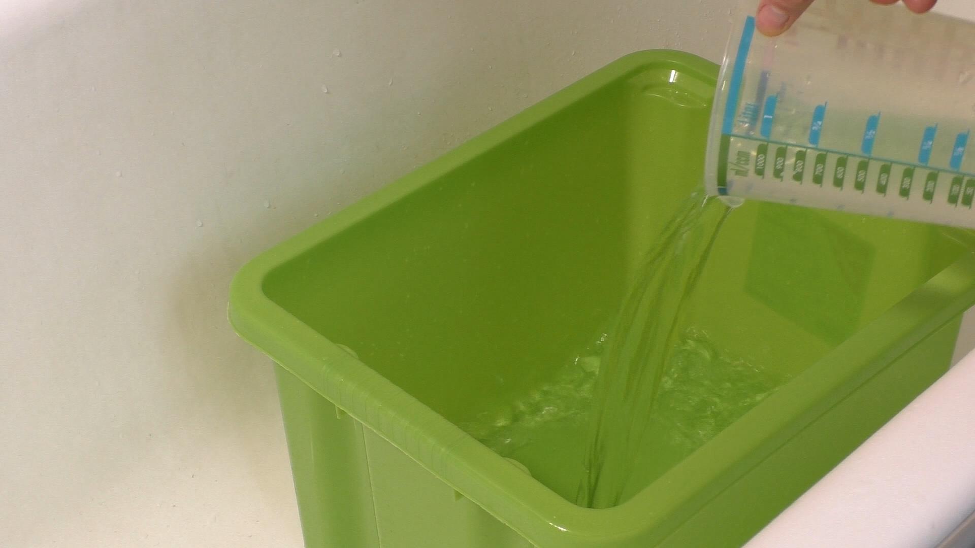 Wasser in Behälter schütten